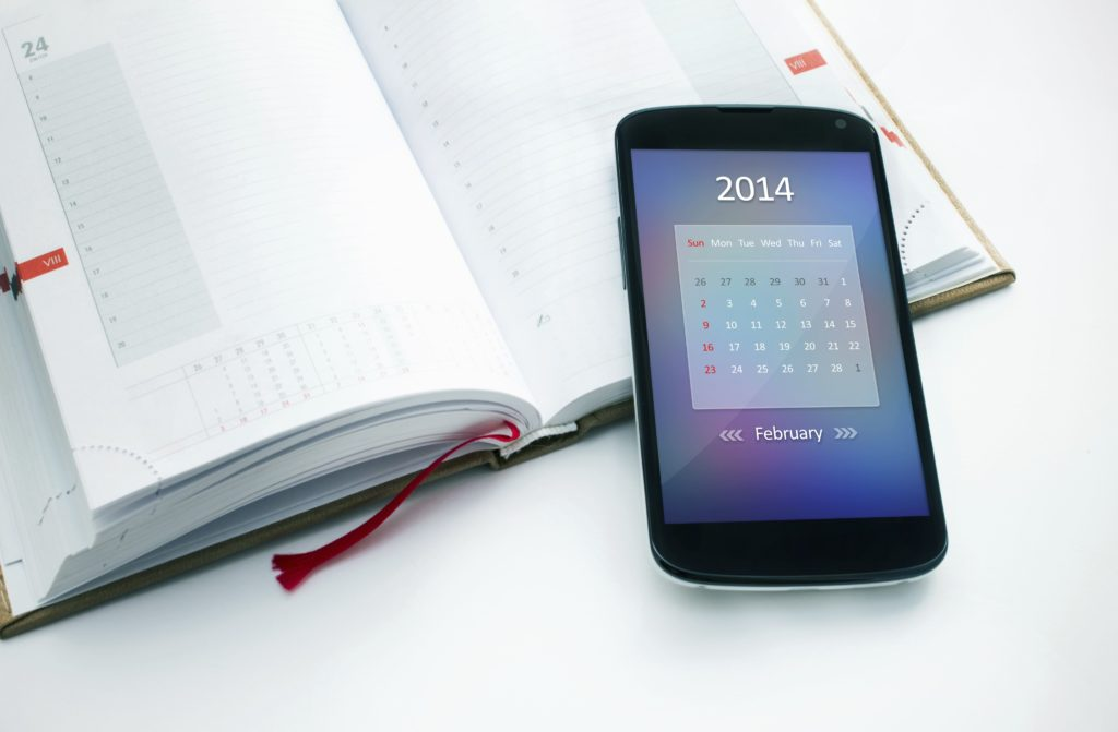 Modern mobile phone with calendar for February 2014.